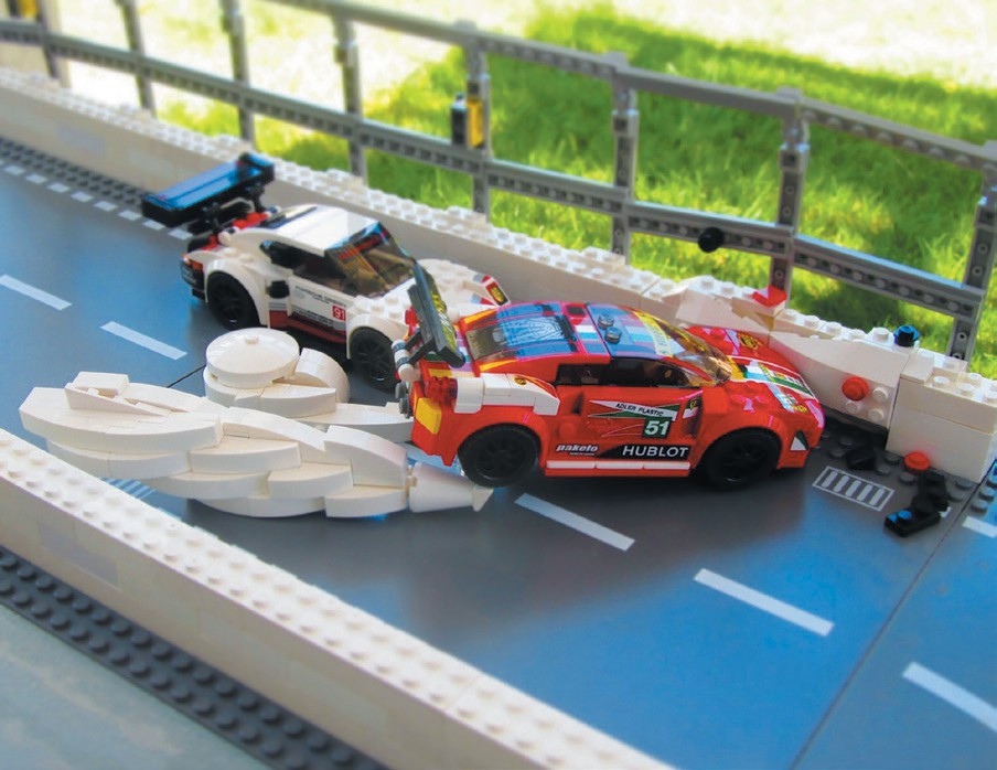 Created by Joseph DeGagne CRASH—The red race car has lost control, tires screeching and smoke billowing, after being struck by the white race car, thus leading to an impact with the retaining wall.