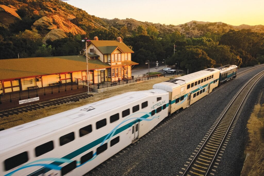 RAILWAY MOTION—At left, an Amtrak train passes the Santa Susana Depot and Museum on July 24. Above, the setting sun bathes a museum exhibit in warm light. The museum has been closed for months because of the coronavirus.