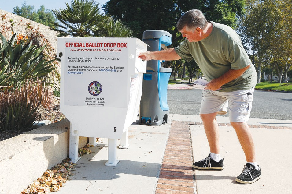 EVERY VOTE COUNTS—Paulette Clements (center) and Mike Flynn (above), both of Simi Valley, return their ballots at the county drop box at the Simi Library. Officials anticipate a record turnout this year.