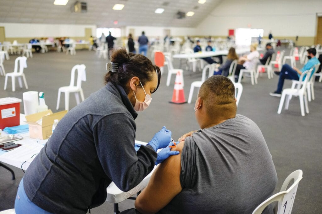 COVETED SHOT—Registered nurse Veronica Silva, left, administers the COVID vaccine to William Fernandez of Oxnard at the Ventura County Fairgrounds Jan. 12 in Ventura MICHAEL COONS/Acorn Newspapers