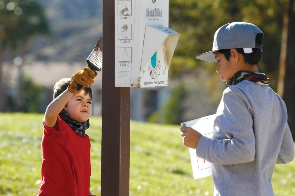 GETTING IT DONE— At left, Collin Langley, 6, of Simi Valley, paints a post as his brother, A.J., 13, puts up a wet paint sign at Rancho Santa Susana Community Park on Jan. 18. They were taking part in the annual MLK Day of Service to honor the legacy of Martin Luther King Jr. At right, Damon Shackelford of Simi spreads bark in the planters at the local park. Below Collin Langley covers his eyes as the Santa Ana winds gust in.