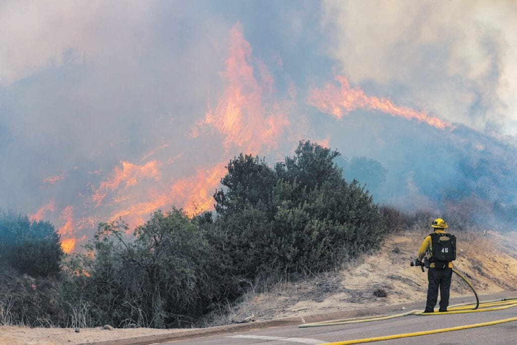 BURNING EARLY—A Ventura County firefighter watches over the Madera fire as it burns toward the 118 Freeway April 1 in Simi Valley. MICHAEL COONS/Acorn Newspapers