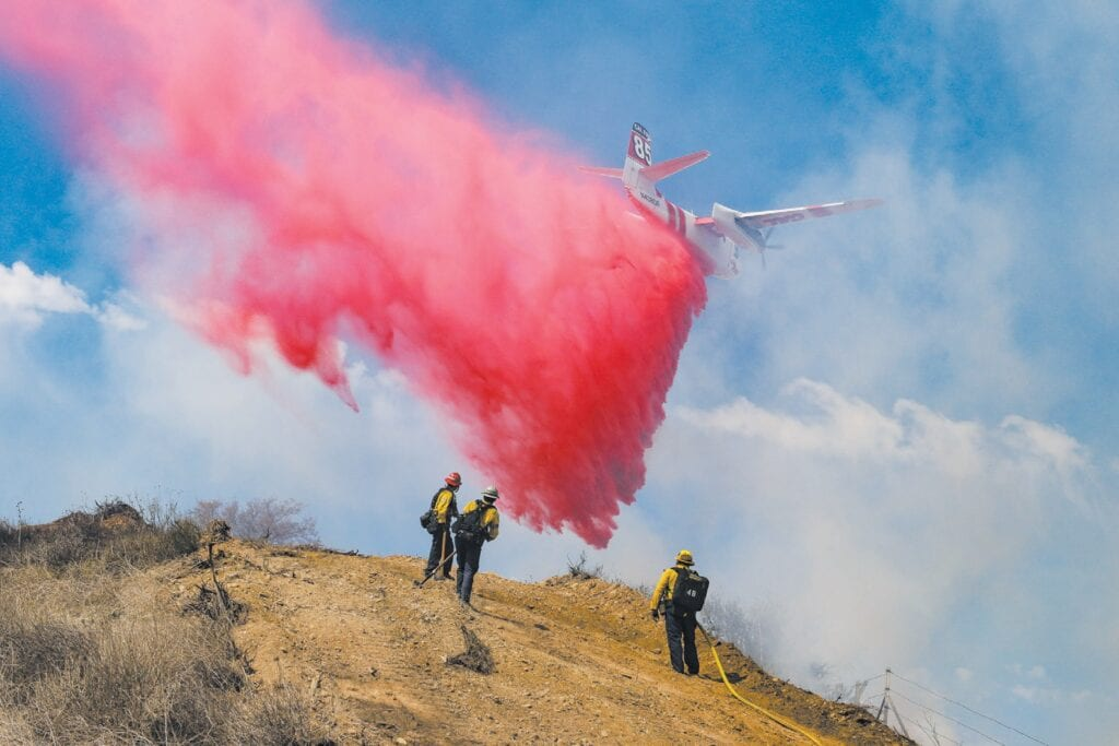 ON IT—A Cal Fire air tanker drops fire retardant on the Madera fire April 1 in Simi Valley. The fire burned more than 16 acres and closed the westbound lanes of the 118 from Madera Road to Collins Drive for a few hours. No injuries or damage to structures were reported. MICHAEL COONS Acorn Newspapers