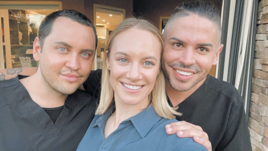 GIFT OF LIFE—Top, Christopher Ogden- Harkins, left, and his husband, Jacob, are pictured June 2 with Danielle Savre, a longtime friend of Christopher's who donated her eggs so the couple could start a family. Above, a pair of jean jackets surrounds a pink onesie and ultrasound photos of Aspen Grey, whose due date is Nov. 26, 2021. Christopher will be Dad and Jacob will be Daddy.