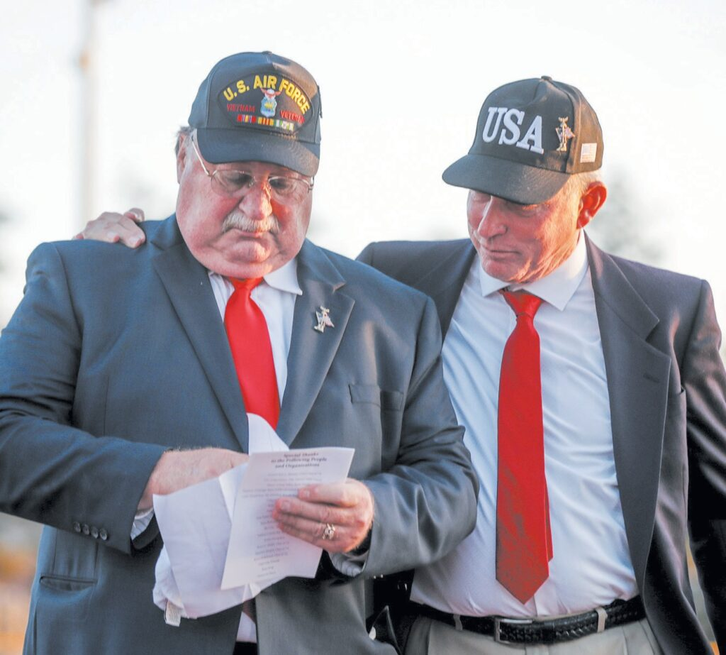 CHOKED UP—Above, Bruce Hellebrand, a member of Simi Valley High's Class of 1972, comforts fellow classmate Bruce Dobin after Dobin gave an emotional speech honoring their classmates who died in Vietnam. At left, Simi Valley High Principal John Baxter is presented the flag before the football game last week.
