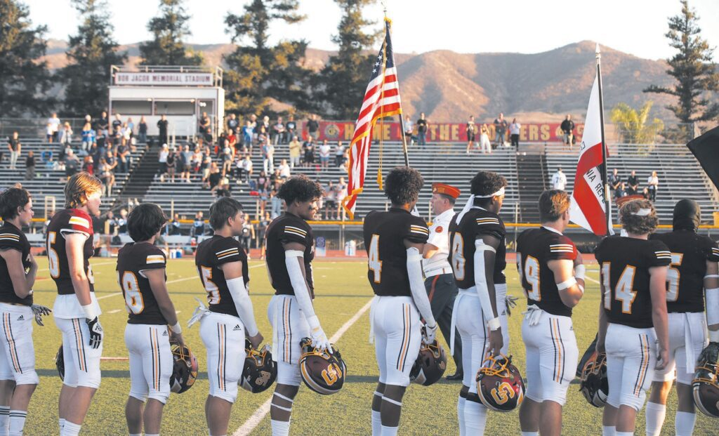 SOLEMN SALUTE—Before the start of Simi Valley High School's Sept. 10 football game, members of the Class of 1972 paid tribute to 10 classmates who went on to serve in Vietnam and were killed in action. Above, members of the school's varsity football team stand at attention during the ceremony as the flag is brought in by the President Ronald Reagan Marine Corps League Detachment #597. Photos by RICHARD GILLARD/Acorn Newspapers
